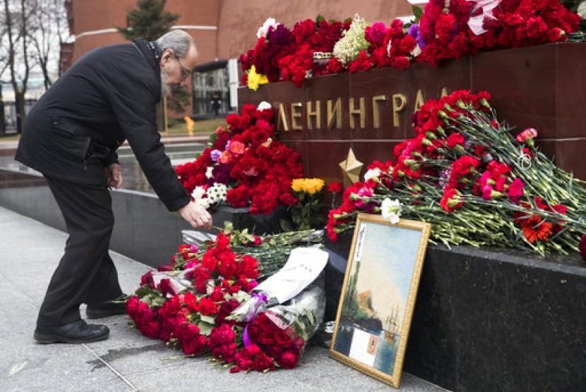 Seorang pria meletakkan bunga mengenang korban ledakan kereta bawah tanah St Petersburg di depan dinding Kremlin di Moskow, Rusia, Selasa (4/4).