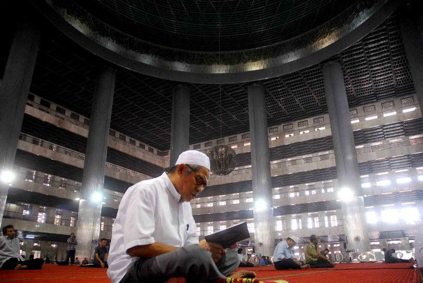 Seorang pria membaca kiab suci Al-Qur'an usai melaksanakan ibadah Shalat Dzuhur di Masjid Istiqlal, Jakarta, Senin (23/7). (Agung Supriyanto/Republika)