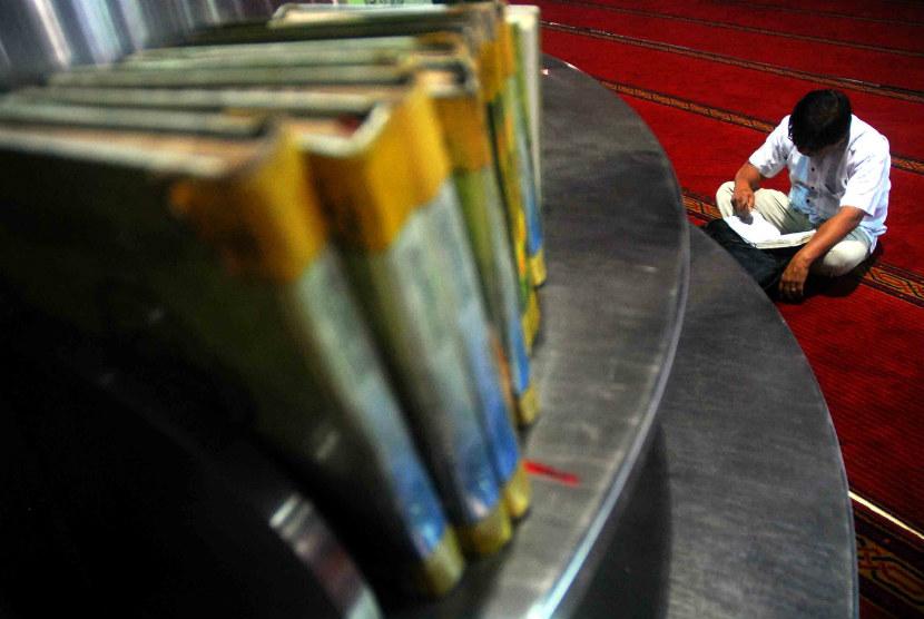 Seorang pria membaca kitab suci Alquran usai melaksanakan ibadah Shalat Dzuhur di Masjid Istiqlal, Jakarta, Senin (23/7). (Agung Supriyanto/Republika)