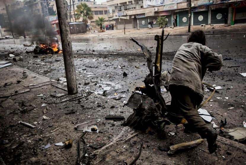 Seorang pria membersihkan pecahan truk yang hancur dihantam roket di sebuah jalan di Distrik Aleppo, Suriah.