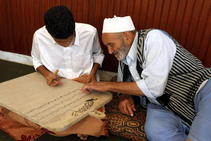Seorang anak membaca sebuah papan tulis kayu sambil menghafal Alquran di Tripoli, Libya, Senin (23/7).   (Ismail Zitouny/Reuters)