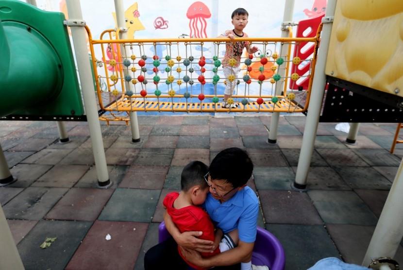 Seorang pria merawat anak dengan autisme di Beijing, Cina. Gangguan autisme lebih banyak ditemukan pada anak laki-laki daripada perempuan.