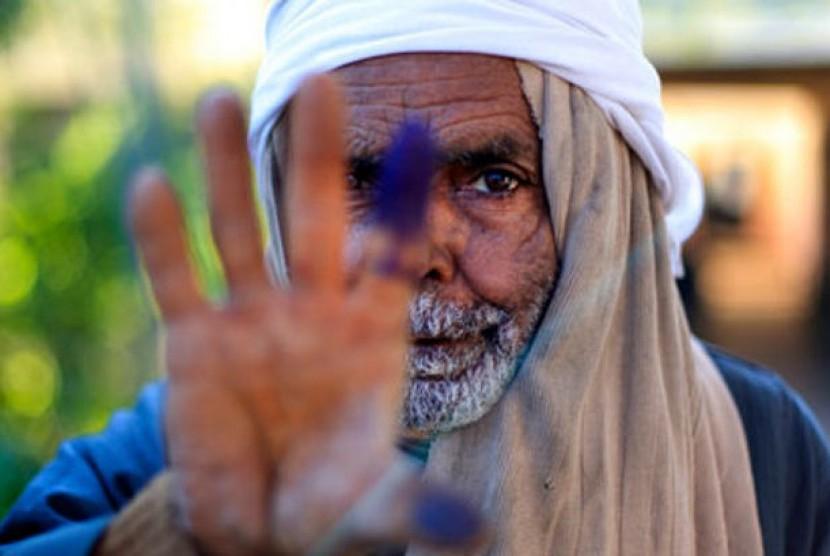 Seorang pria Mesir menunjukkan jari kirinya usai memberikan suara dalam referendum tahap kedua atas konstitusi baru.