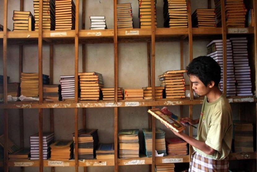 Seorang santri membersihkan koleksi Kitab Kuning di Pondok Pesantren Petuk, Kediri, Jawa Timur.