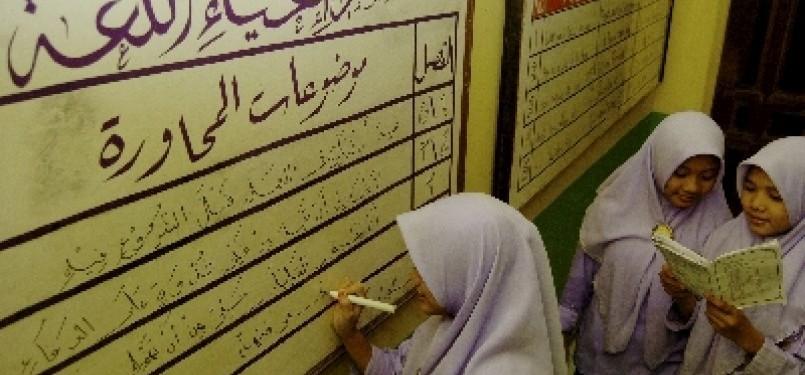 Seorang santri menulis aksara Arab di sebuah papan bahasa/Ilustrasi