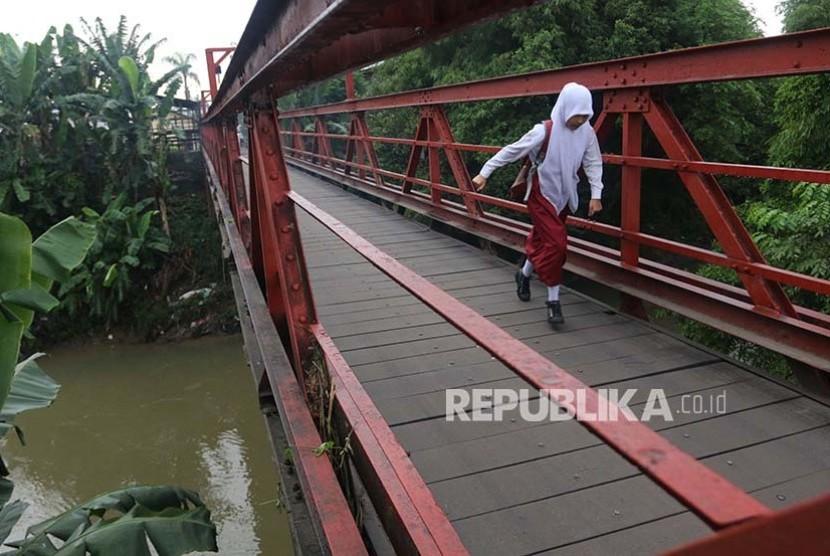 Seorang siswa SD berlari di jembatan saat akan ke sekolah untuk mengikuti Ujian Nasional (UN) di Desa Klambir V, Deli Serdang, Sumatera Utara, Senin (15/5). Ujian Nasional tingkat SD dilaksanakan secara serentak pada 15 - 17 Mei 2017.