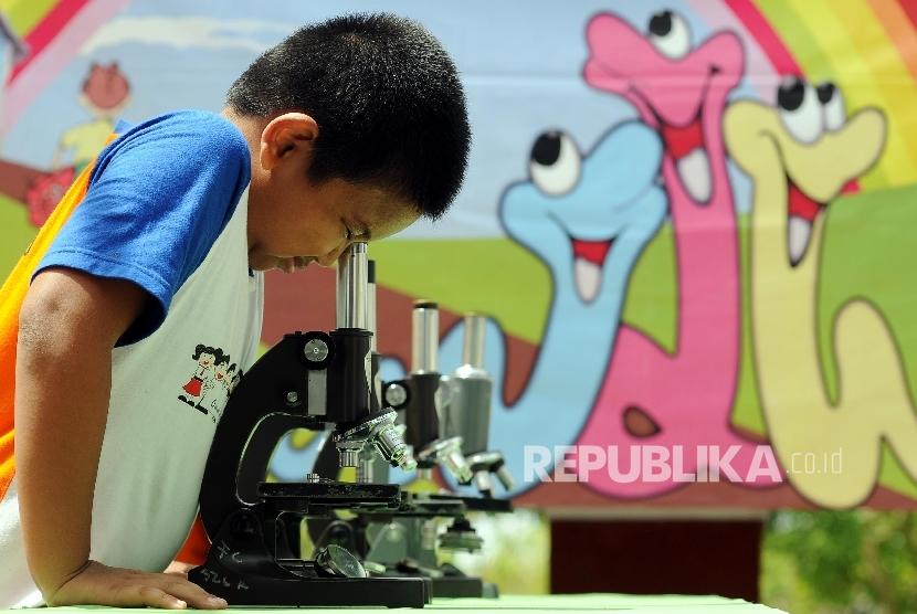 Seorang siswa SD melihat cacing kremi dengan alat mikroskop saat kegiatan sosialisasi pencegahan terhadap bahaya caingan pada anak-anak.