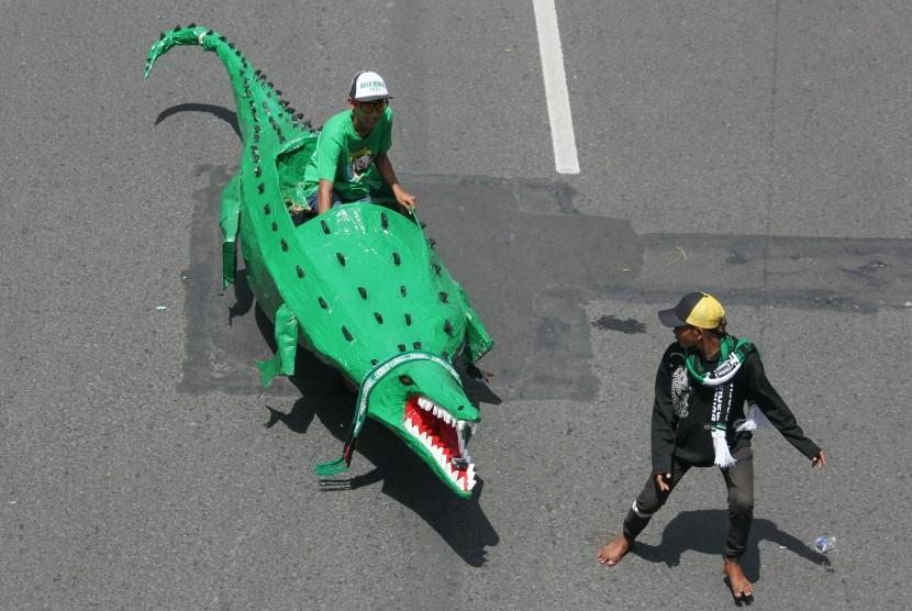 Seorang suporter Persebaya Surabaya mengendarai replika Buaya saat Parade Bela Persebaya di Surabaya. (ilustrasi)