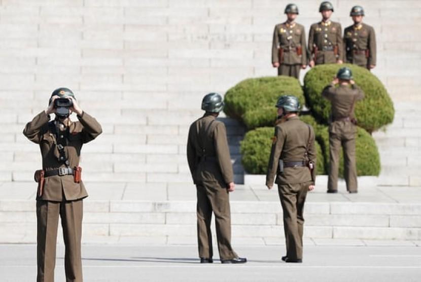 Seorang tentara Korea Utara melihat Desa Panmunjom di Paju, Korea Selatan yang berbatasan dengan Korut melalui teropong.
