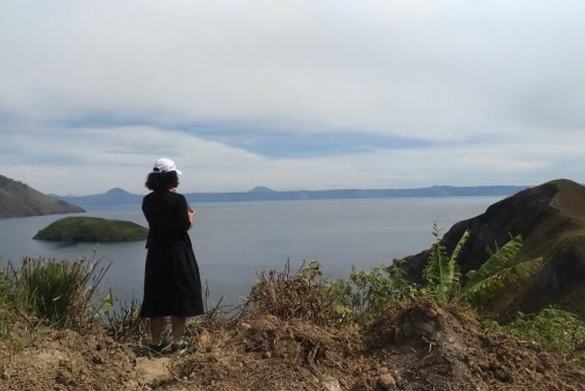 Seorang turis lokal memandangi keindahan Danau Toba dari atas bukit.