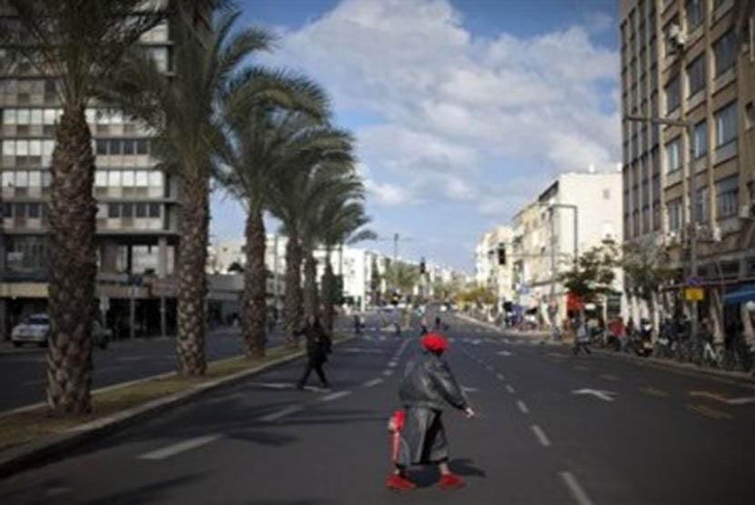 Seorang wanita Israel melintasi jalan di Tel Aviv, Israel, Jumat (9/12).