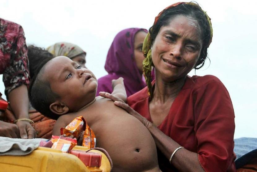 Seorang wanita muslim Rohingya Myanmar berada dalam sebuah perahu bersama bayinya dalam pelariannya ke Bangladesh untuk menghindari kekerasan antara umat Buddha lokal dan Muslim Rohingya. Muslim Rohingya ini dicegat oleh otoritas perbatasan Bangladesh di T
