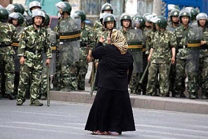 Seorang wanita Muslim Uighur di Urumqi, Xinjiang, berhadapan dengan militer Cina