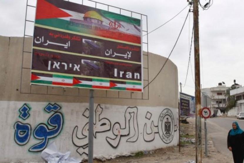 Seorang wanita Palestina berjalan melewati baliho yang bertuliskan 'Terima Kasih Iran' di Kota Gaza, Palestina, Selasa (27/11)