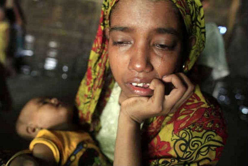 Seorang wanita pengungsi Rohingya menangis sambil menggendong bayinya.