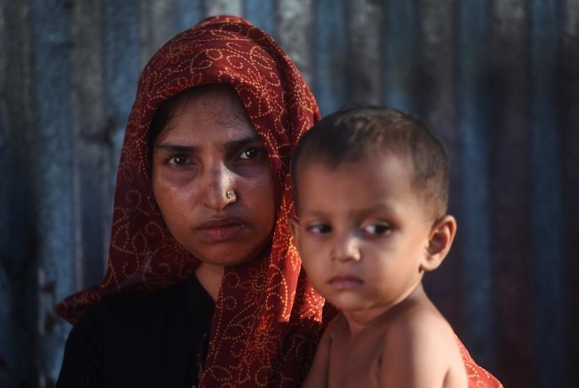 Seorang wanita pengungsi Rohingya menggendong anaknya di Kamp Pengungsian Kutupalong, Cox Bazar, Bangladesh, Minggu (1/10).