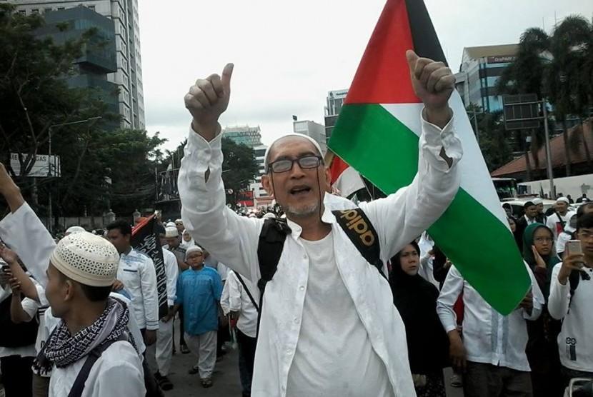 Seorang warga asal Bandung Otje Ardawilaga mengacungkan jempol di tengah acara aksi Bela Palestina di Lapangan Monas, Jakarta, Ahad (17/12).