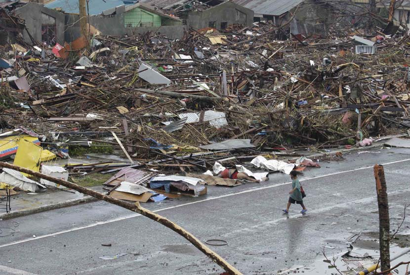 Seorang warga berjalan melewati pemukiman yang hancur akibat Topan Haiyan di kota Tacloban, Leyte provinsi Leyte, Filipina tengah, Ahad (10/11).  (AP/Bullit Marquez)
