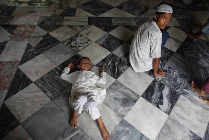 Seorang warga etnis Rohingya tengah menunggu bantuan diluar sebuah masjid di Sittwe, Myanmar.   (Damir Sagolj/Reuters)