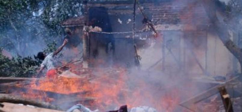 Seorang warga melemparkan batu ke arah bangunan rumah, musholla dan madrasah yang dibakar massa, di Desa Blu'uran, Karangpinang, Sampang, Madura, Jatim, Kamis (29/12).