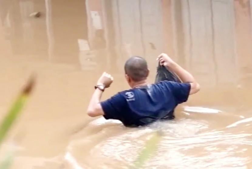 Seorang warga melintasi jalan yang sudah tertutup oleh banjir di Jakarta