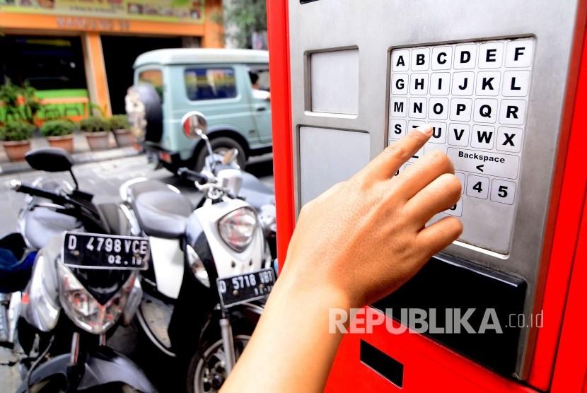 Seorang warga membayar parkir di tempat mesin smartparking, Jalan Braga, Kota Bandung, Kamis (5/10).