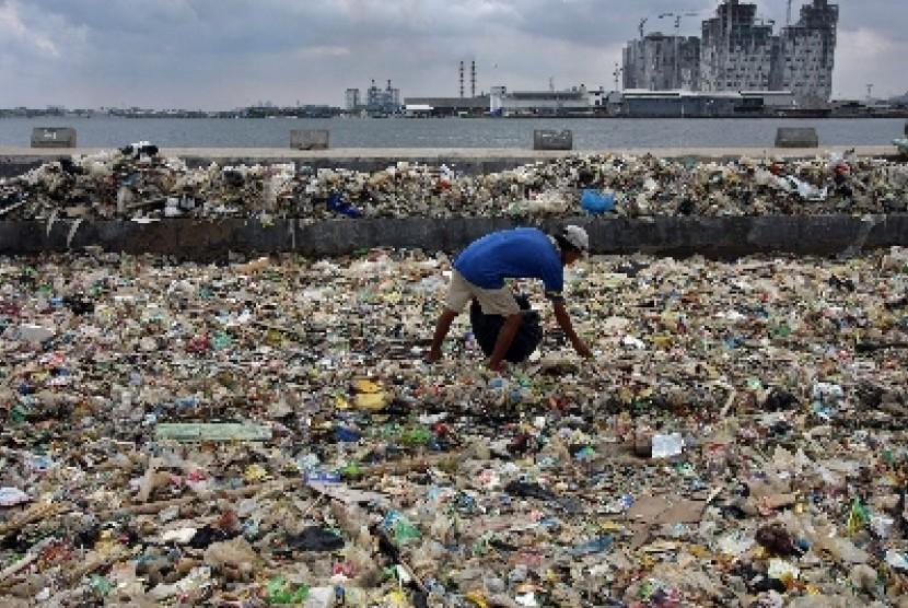 Seorang warga memilah sampah plastik yang menumpuk di bibir pantai Muara Angke, Jakarta Utara, Senin (30/1). Kondisi penumpukan sampah yang tak terkendali tersebut menyebabkant air laut menjadi tercemar yang berdampak buruk bagi lingkungan.