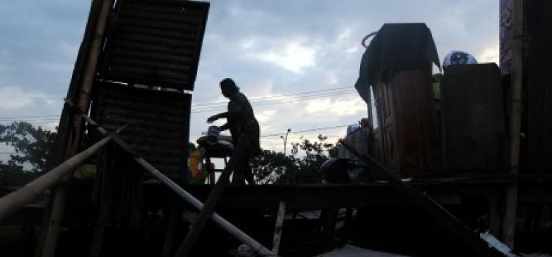 Seorang warga merapikan rumahnya yang rusak akibat diterjang angin puting beliung di kelurahan Kassi-kassi Makassar, Sulsel, Sabtu (26/11). Sekitar 50 rumah rusak akibat diterjang angin puting beliung di Makassar.