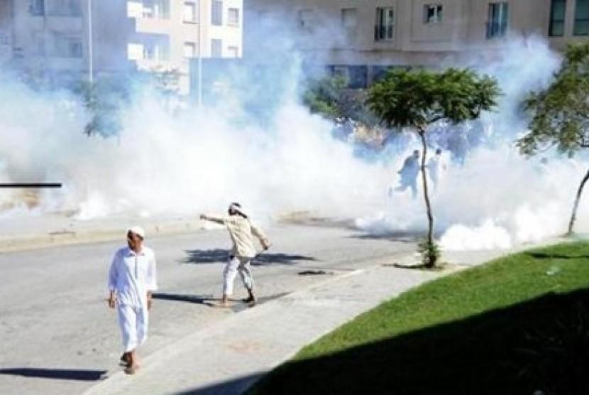 Seorang warga Tunisia melempar batu dalam aksi protes di depan Kedutaan Besar AS di Tunis, Jumat (14/9/2012)