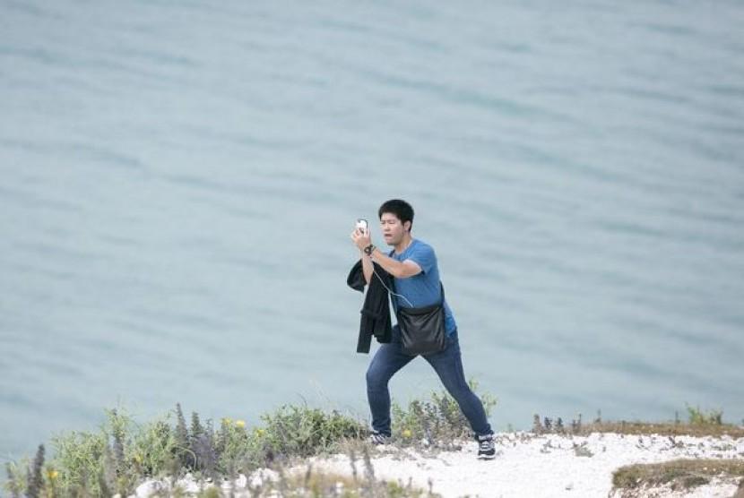 Seorang wisatawan asik selfie di pinggiran tebing tinggi. Tidak jarang wisatawan membahayakan diri sendiri demi mendapatkan foto yang bagus saat berlibur