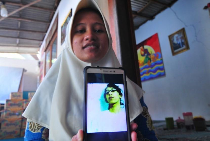 Sianit Sinta menujukkan foto alhamrhum suaminya Ahmad Budi Cahyanto, guru SMAN 1 Torjun yang tewas dipukul siswanya sendiri, di Desa Tanggumung, Sampang, Jawa Timur, Sabtu (3/2).