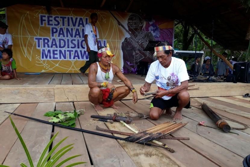 Sikerei atau dukun yang dihormati dalam tradisi Suku Mentawai menunjukkan cara pembuatan racun untuk berburu hewan.
