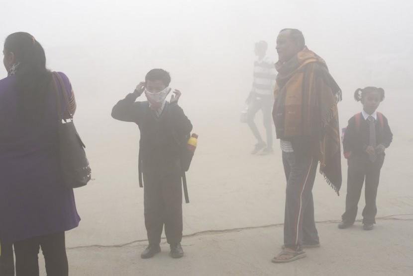 Siswa India menggunakan sapu tangan sebagai masker untuk melindungi diri dari polusi udara mematikan di New Delhi, India.