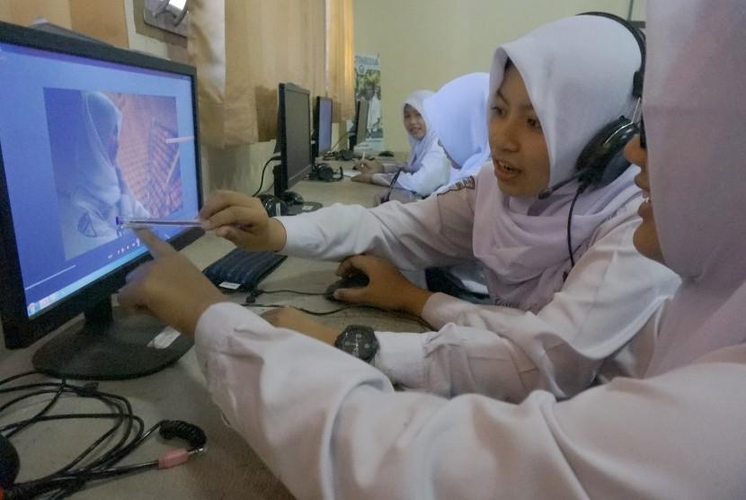 Siswa mengikuti pelajaran praktikum di laboratorium multimedia SMKN 1 Tulungagung, Tulungagung, Jawa Timur, Senin (24/7). Sebanyak enam lembaga yang terdiri dari tiga SMA dan tiga SMK di daerah itu mulai menguji coba pelaksanaan pola pembelajaran lima hari sekolah.