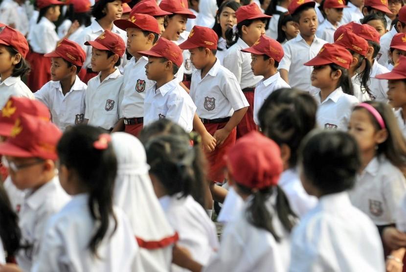 Siswa sekolah dasar berjalan menuju ruang kelas mereka saat hari pertama masuk sekolah pada tahun ajaran baru.