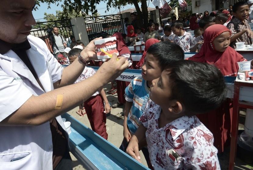Siswa Sekolah Dasar memperhatikan cara menyikat gigi yang baik saat mengikuti kegiatan Bulan Kesehatan Gigi Nasional (BKGN) 2015 di Rumah Sakit Gigi & Mulut Kandea Universitas Hasanuddin, Makassar, Sulawesi Selatan, Kamis (8/10).