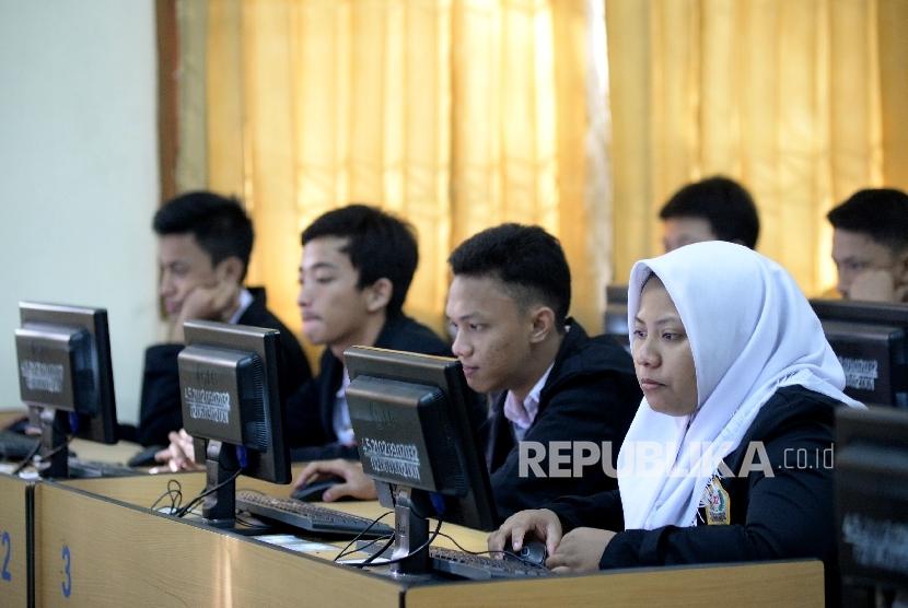 Siswa-siswi mengikuti Ujian Nasional Berbasis Komputer (UNBK) di Sekolah Menengah Kejuruan (SMK) Negeri 32 Jakarta, Senin (3/4).