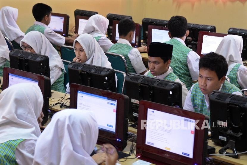 Siswa-siswi MTSN 3 Jakarta, mengerjakan soal ujian mata pelajaran bahasa Indonesia saat Ujian Nasional Berbasis Komputer (UNBK), Senin (9/5).