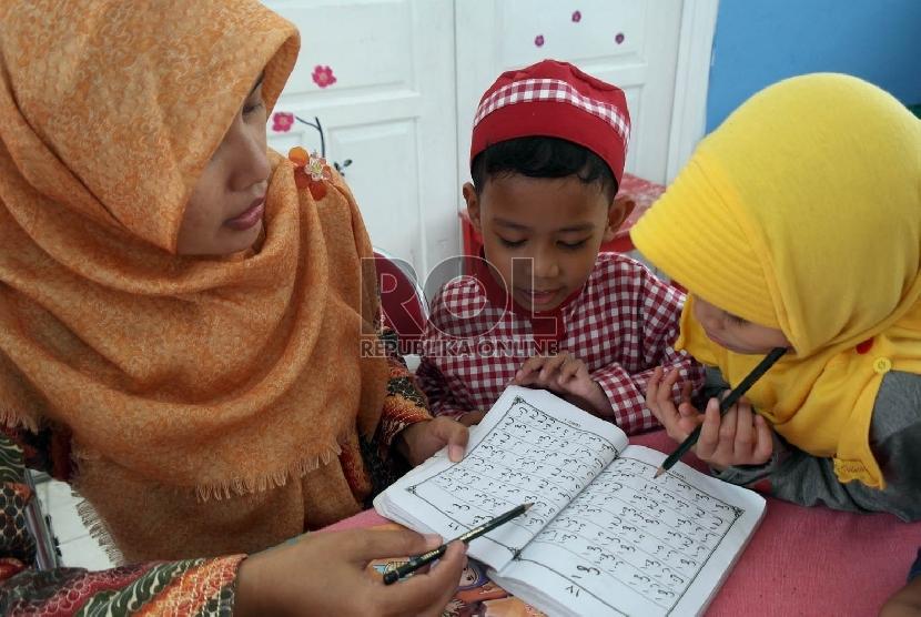 Seorang guru sedang mengajarkan membaca huruf arab