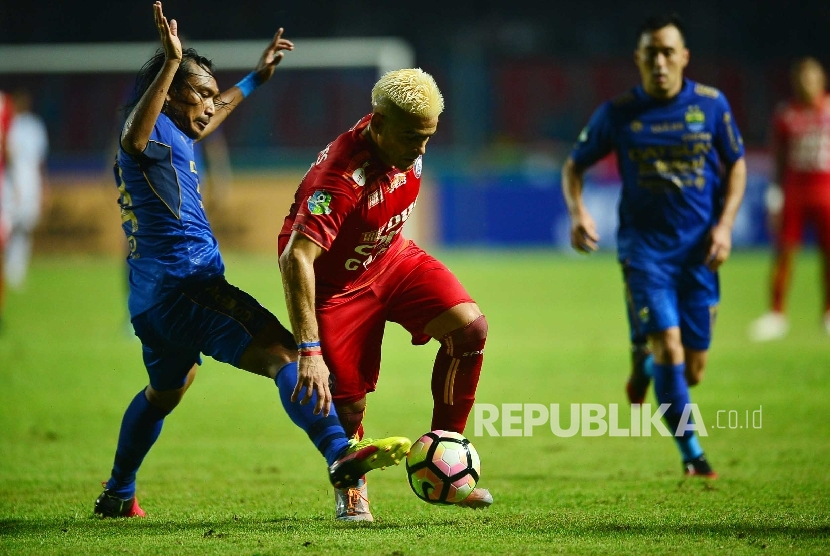 Striker Arema FC, Cristian Gonzales (tengah) berusaha melewati gelandang Persib Bandung Hariyono dalam laga Liga 1 di stadion Gelora Bandung Lautan Api, Bandung, Sabtu (15/4). Gonzales bakal absen saat timnya menjamu Bhayangkara FC akhir pekan ini.