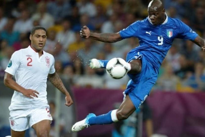 Striker Italia Mario Balotelli menendang bola ke gawang, sementara bek Inggris Glen Johnson cuma bisa menyaksikan