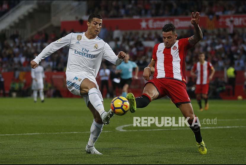 Striker Real Madrid Cristiano Ronaldo berebut bola dengan pemain Girona Aday Benitez pada pertandingan  Laliga di Montilivi stadium in Girona, Spanyol.