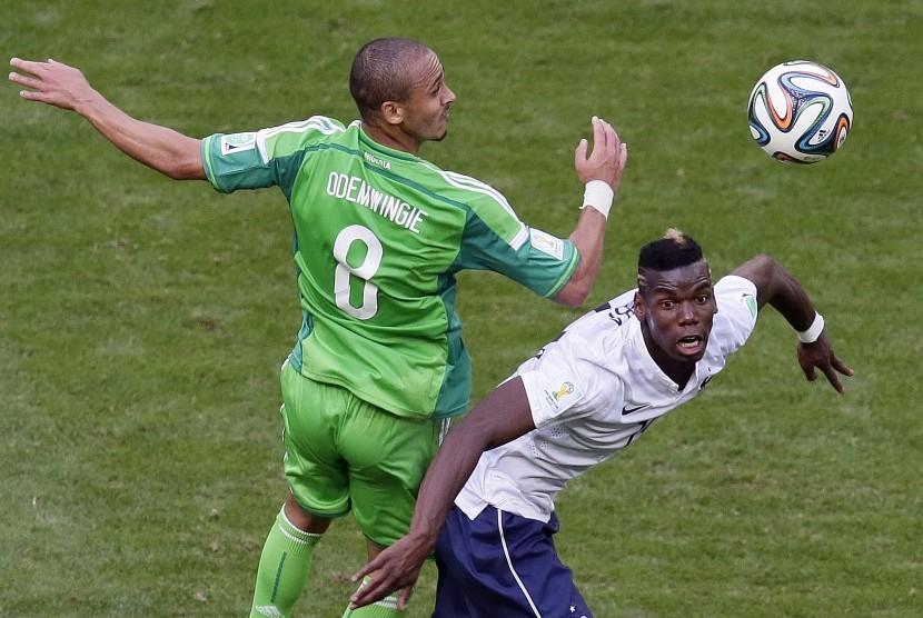 Striker timnas Nigeria, Peter Odemwingie (kiri) berebut bola dengan Paul Pogba pada laga Piala Dunia 2014. Odemwingie tengah diincar Madura United.
