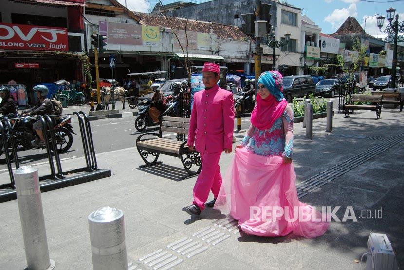 Suami dan Istri yang berperan sebagai model memperagakan busana pernikahan Muslim di Malioboro, Yogyakarta, Kamis (30/3).