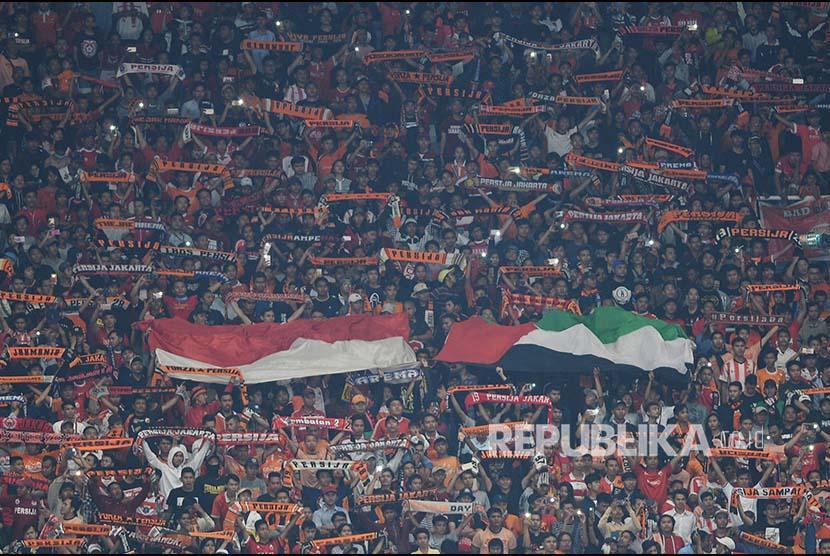 Suporter membentangkan bendera dan syal dalam laga kedua Grup H Piala AFC antara Persija Jakarta melawan Tampines Rovers di Stadion Utama Gelora Bung Karno, Jakarta, Rabu (28/2). Persija berhasil menang dengan skor 4-1.