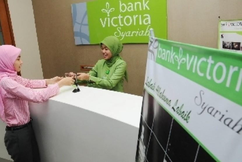 Teller melayani nasabah di Bank Victoria Syariah, Senayan, Jakarta.