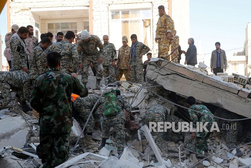 Tentara Iran mencari korban di bangunan yang hancur akibat gempa di kota Sarpol-e-Zahab di Provinsi Kermanshah, Iran, Senin (13/11). Gempa berkekuatan 7,2 besar melanda wilayah tersebut di sepanjang perbatasan antara Iran dan Irak pada (12/11), menewaskan sedikitnya 129 orang dan melukai lebih dari 300.