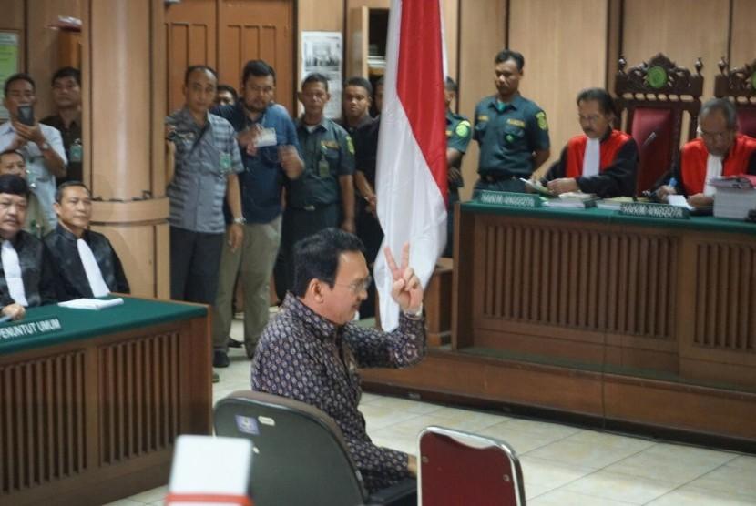 Terdakwa kasus dugaaan penistaan agama Basuki Tjahaja Purnama (Ahok) memberikan salam dua jari saat memasuki ruang sidang Koesumah Atmadja, Eks Gedung Pengadilan Negeri Jakarta Pusat, Selasa (27/12).