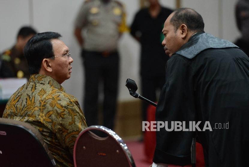 Terdakwa kasus dugaan penistaan agama Basuki Tjahaja Purnama berbincang bersama kuasa hukumnya saat menjalani sidang lanjutan dengan agenda pembacaan tuntutan di ruang auditorium Kementerian Pertanian, Jakarta, Selasa (11/4).