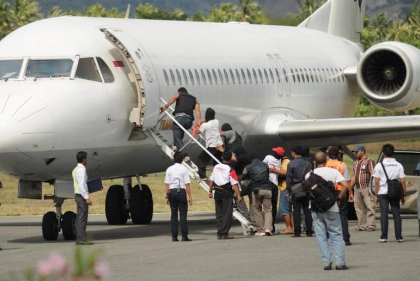 TERDUGA TERORIS. Petugas menaikkan sejumlah orang yang diduga sebagai terduga teroris ke dalam pesawat khusus di Bandara Mutiara Palu, Sulawesi Tengah, Rabu (31/10).
